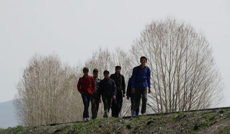 Group of Afghan migrants walk along a main road after crossing the Turkey-Iran border near Erzurum