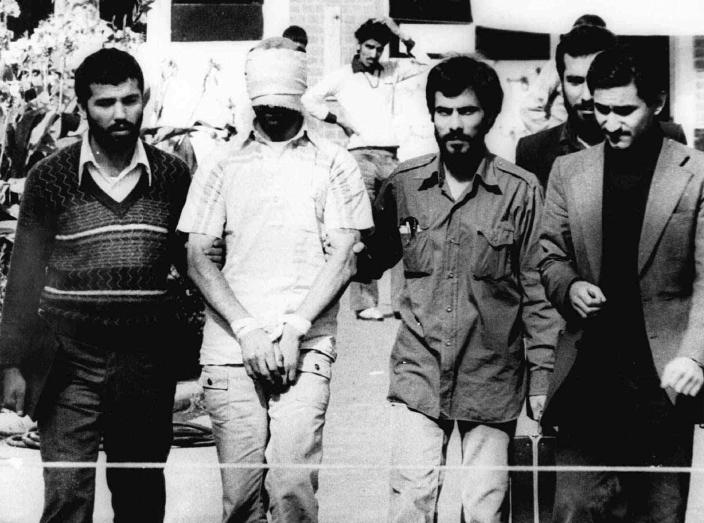 FILE - In this Nov. 9, 1979, file photo, one of the hostages being held at the U.S. Embassy in Tehran is displayed blindfolded and with his hands bound to the crowd outside the embassy. The U.S. and Iran cut off diplomatic ties in 1979 after the Islamic Revolution and the storming of the U.S. Embassy in Tehran, where 52 Americans were held hostage for more than a year. Since his inauguration in 2009, President Barack Obama has expressed a willingness to meet with the Iranians without conditions. The U.S. and Iran secretly engaged in high-level, face-to-face talks, at least three times over the past year, in a high stakes diplomatic gamble by the administration that paved the way for the historic deal aimed at slowing Iran's nuclear program. (AP Photo/File)
