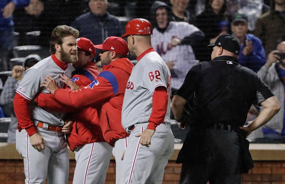 Philadelphia Phillies' Bryce Harper, left, is restrained while arguing with umpire Mark Carlson, right, during the fourth inning of a baseball game against the New York Mets, Monday, April 22, 2019, in New York. (AP Photo/Frank Franklin II)
