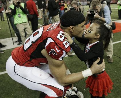 Atlanta Falcons tight end Tony Gonzalez kisses his daughter during a celebration of his career before the second half of an NFL football game against the Carolina Panthers, Sunday, Dec. 29, 2013, in Atlanta. (AP Photo/Dave Martin)