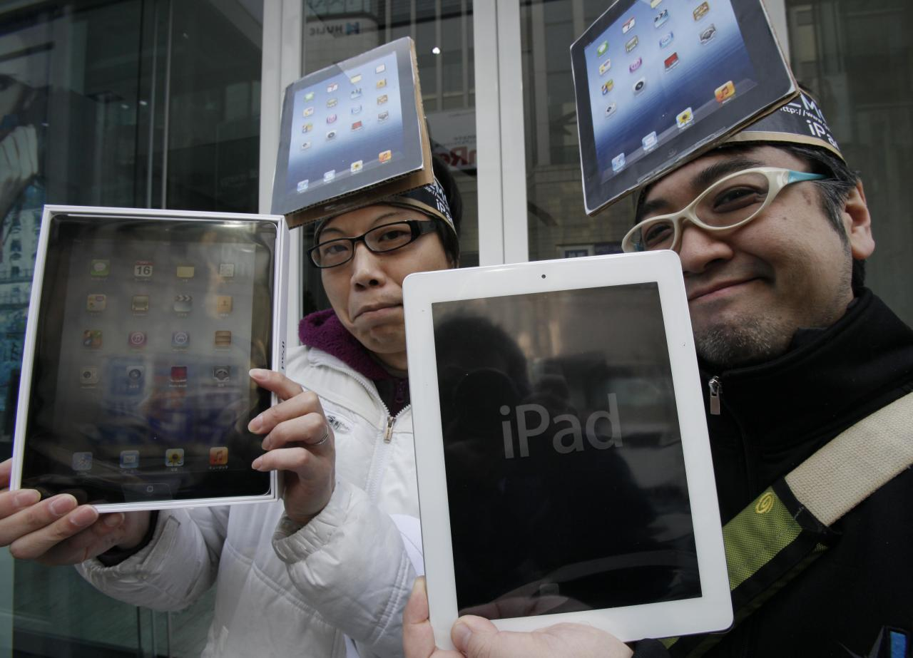 Japanese Ryota Musha, 41, right, and Hisanori Kogure, 31, show off new iPad tablet computers they purchased, in Tokyo Friday, March 16, 2012. Sales of the third version of Apple's iPad began Friday morning in Japan. (AP Photo/Koji Sasahara)