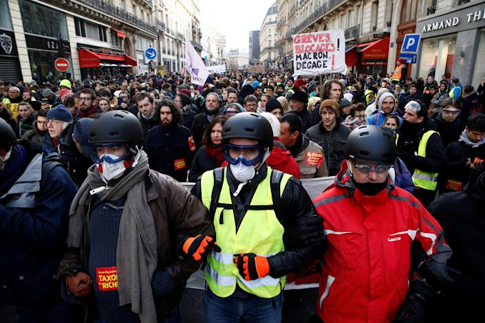 """Protesters wearing yellow vests and demonstrators attend a demonstration during a national day of protest by the """"yellow vests"""" movement in Paris, France, Dec. 8, 2018. (Photo: Stephane Mahe/Reuters)"""