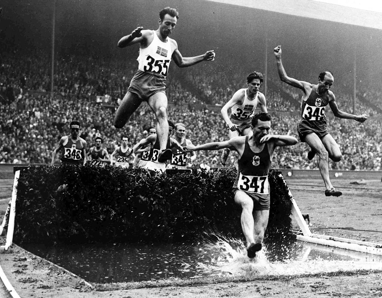 Competitors in the men's Olympic Games 3,000-metres Steeplechase Final, at Wembley Stadium, London, Aug. 5, 1948, jump over the water jump. From left to right; Erik Elmsater of Sweden, number 355; Thore Sjoestrand of Sweden, number 357, centre rear; M. Chesneau of France, number 347; Alex Guyodo of France, number 348. (AP Photo)