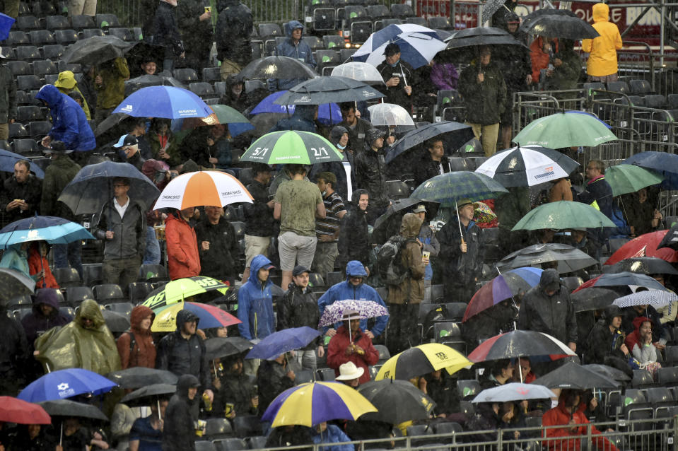 Spectators hold umbrellas after rain stopped play during the third one day international cricket match between England and Sri Lanka, at Bristol County Ground in Bristol, England, Sunday, July 4, 2021. (AP Photo/Rui Vieira)
