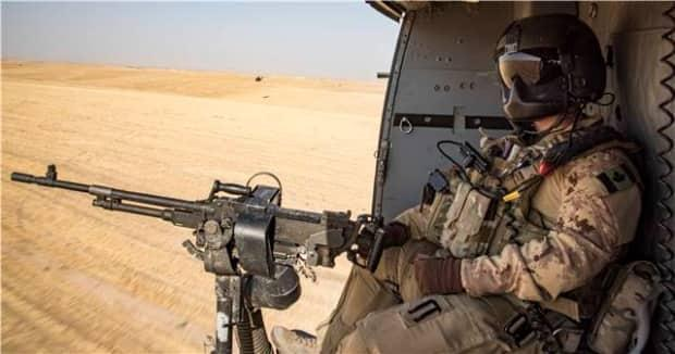 A door gunner with the tactical aviation detachment watches out of a CH-146 Griffon helicopter during Operation IMPACT on September 27, 2017.  (Combat Camera/DND - image credit)