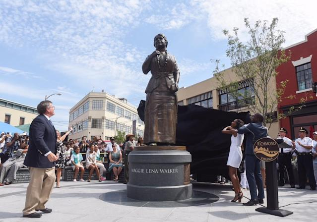 Sculptor Toby Mendez, left, watches Liza Mickens, the great-great-granddaughter of Maggie Walker, and Mayor Levar Stoney unveil a new statue to Walker in Richmond, Va., on July 15, 2017. (Photo: Scott Elmquist/Style Weekly)