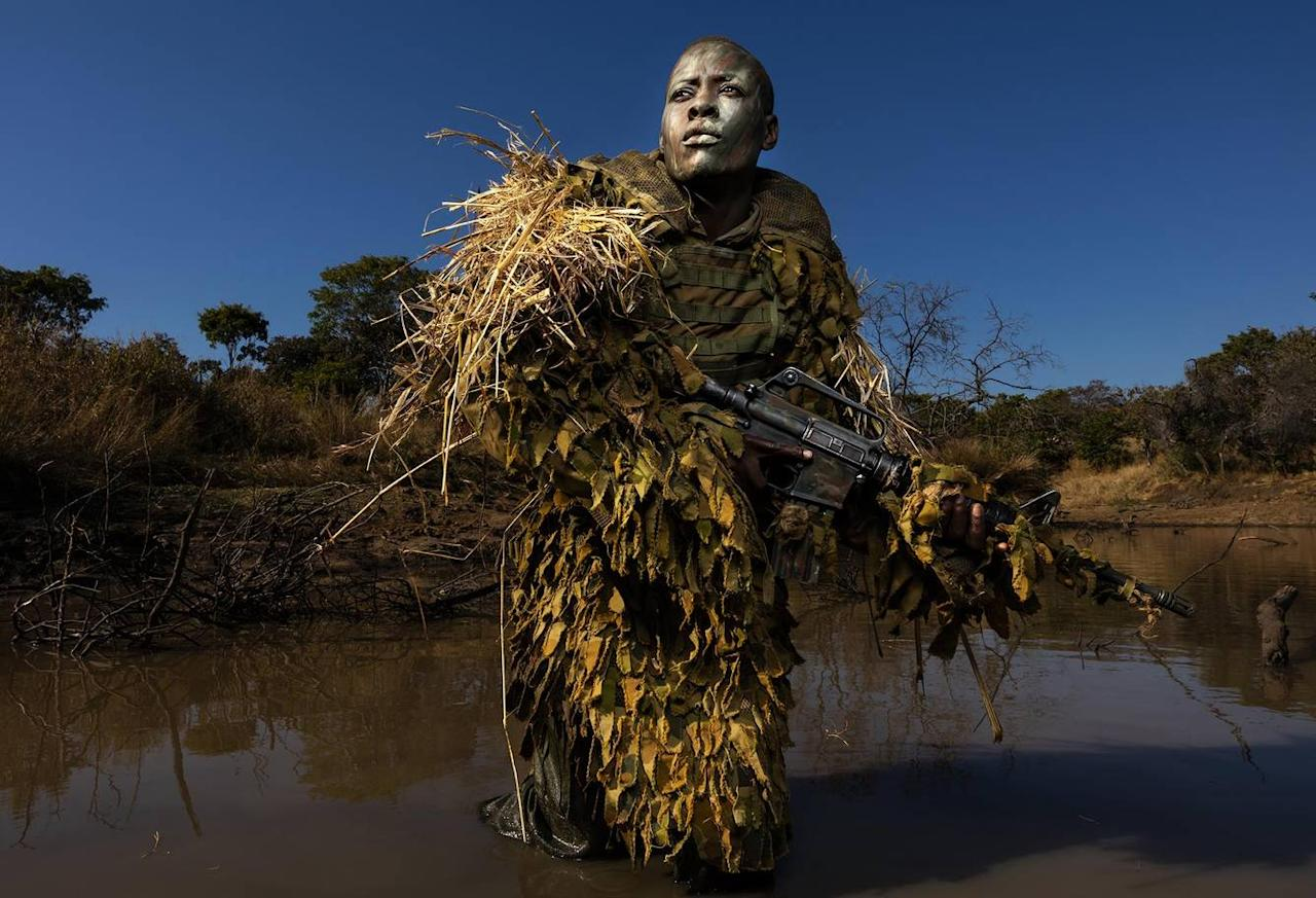 <p>Petronella Chigumbura (30), a member of an all-female anti-poaching unit called Akashinga, participates in stealth and concealment training in the Phundundu Wildlife Park, Zimbabwe. (Brent Stirton/Getty) </p>