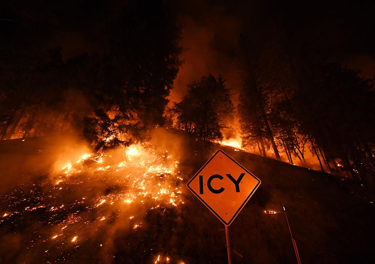 A road sign warns for ice as the Carr Fire continues to spread toward the towns of Douglas City and Lewiston near Redding, California.