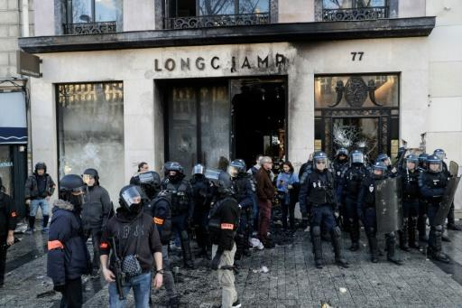Riot police outside a partially burned Longchamps store on the Champs-Elysees in Paris on Saturday