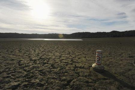 A buoy meant for boaters rests on the dry bed of Lake Mendocino , in California