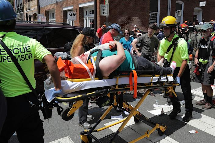 <p>Rescue workers move victims on stretchers after car plowed through a crowd of counter-demonstrators marching through the downtown shopping district Aug. 12, 2017 in Charlottesville, Va. (Photo: Chip Somodevilla/Getty Images) </p>