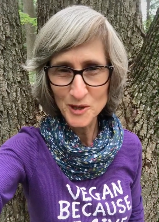 Pictured is vegan activist Miss Kadie appearing in a TikTok video while standing in front of a tree.
