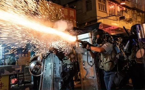 Police fire tear gas to clear pro-Democracy protesters during a demonstration on Hungry Ghost Festival day in the Sham Shui Po district - Credit: Getty