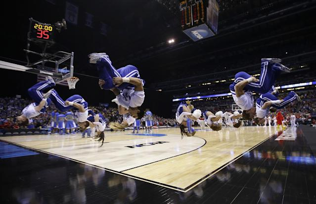 Kentucky cheerleaders flip before an NCAA Midwest Regional semifinal college basketball tournament game against the Louisville Friday, March 28, 2014, in Indianapolis. (AP Photo/David J. Phillip)
