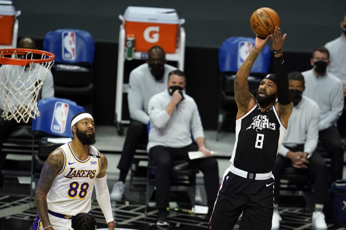 Los Angeles Clippers forward Marcus Morris Sr., right, shoots over Los Angeles Lakers forward Markieff Morris, left, during the first half of an NBA basketball game Sunday, April 4, 2021, in Los Angeles. (AP Photo/Marcio Jose Sanchez)