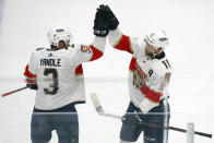 Florida Panthers defenseman Keith Yandle (3) high-fives left wing Jonathan Huberdeau (11) who scored against the Dallas Stars in the first period during an NHL hockey game on Sunday, March 28, 2021, in Dallas. (AP Photo/Richard W. Rodriguez)