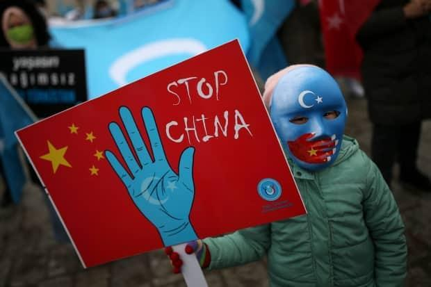 A protester from the Uyghur community living in Turkey holds an anti-China placard during a protest in Istanbul on Thursday, March 25.
