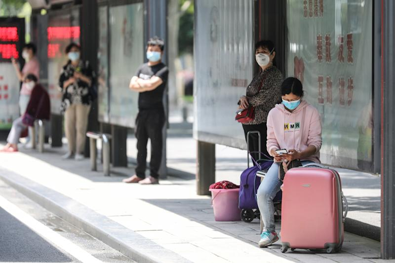People wait at a bus station in Wuhan in China's central Hubei province on May 11, 2020. - China reported a second day of new cases of coronavirus in Wuhan on May 11 after a month without new infections at the pandemic's global epicentre, offering a stark warning of the dangers of a fresh wave. (Photo by STR / AFP) / China OUT (Photo by STR/AFP via Getty Images)