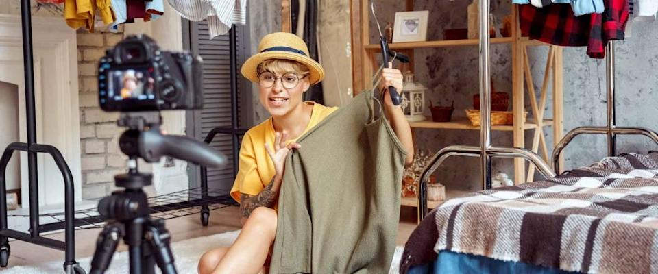 Young woman fashion blogger influencer wearing hat and eyeglasses sitting on fluffy carpet at urban stylish apartment recording video vlog on digital camera telling clothing tips