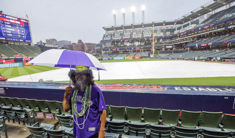 Gregory Espinosa of Farmington, N.M. waits out a rain delay before a Cleveland Indians baseball game against the Texas Rangers in Cleveland, Tuesday, Aug. 6, 2019. The game was eventually postponed. (AP Photo/Phil Long)