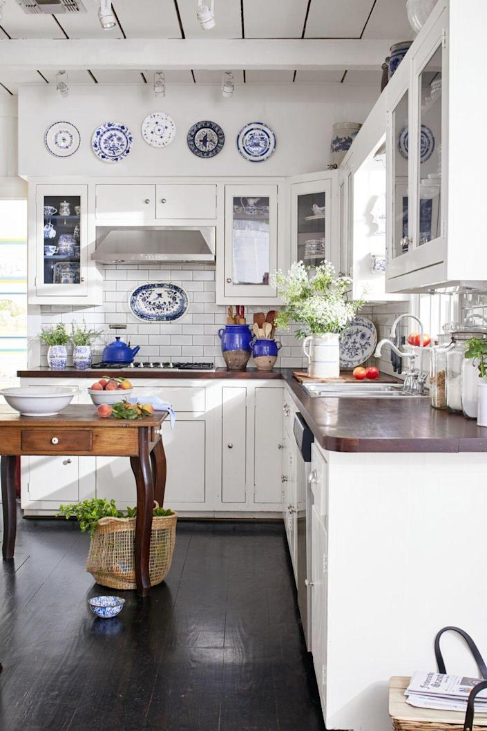 <p>This kitchen looks like it's modeled after the blue and white plates hanging on the wall, with bold touches of royal blue throughout the room. </p>