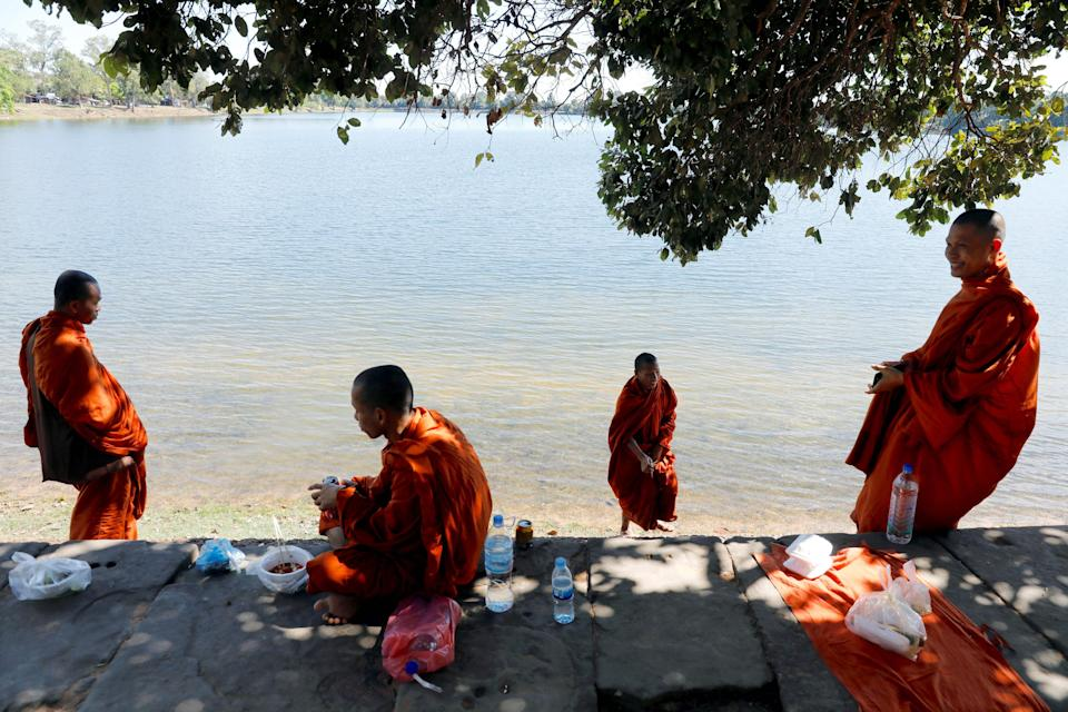 Buddhist monks have a lunch next to a lake. Photo: REUTERS/Jorge Silva