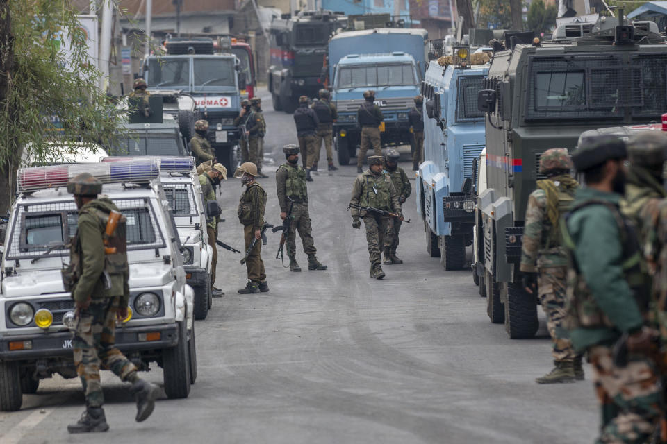 Indian army soldiers and policemen stand guard near the site of a gun battle on the outskirts of Srinagar, Indian controlled Kashmir, Sunday, Nov. 1, 2020. According to police, Indian government forces killed Saifullah Mir, a top rebel commander of the region's largest rebel group, Hizbul Mujahideen which has spearheaded an armed rebellion against Indian rule for decades. (AP Photo/ Dar Yasin)