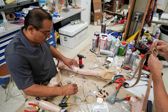 <p>A worker prepares a prosthetic arm during a fitting at the Shriners Hospital in Philadelphia, Pa., on May 30, 2017. (Photo: Carlo Allegri/Reuters) </p>