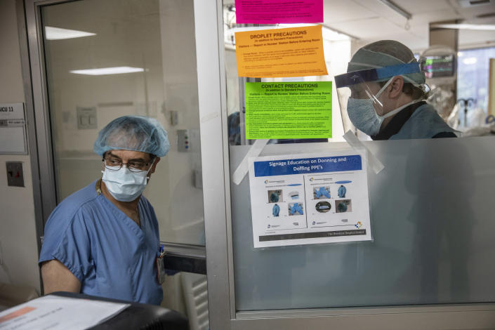Dr. George Nerantzakis, left, and Will Vanderwall, a physician assistant, prepare to perform a procedure for a patient stricken with the coronavirus at the Brooklyn Hospital Center in New York, March 30, 2020. (Victor J. Blue/The New York Times)