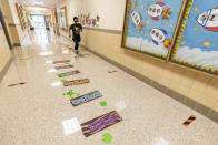 A student runs down a hallway with markers for proper social distancing during the coronavirus outbreak at the Post Road Elementary School, Thursday, Oct. 1, 2020, in White Plains, N.Y. (AP Photo/Mary Altaffer)