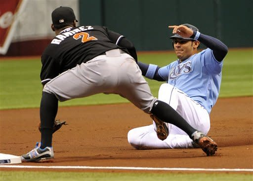 Tampa Bay Rays' Carlos Pena, right, gets caught at third by Miami Marlins third baseman Hanley Ramirez as he attempted to advance from first base off teammate Hideki Matsui's single during the first inning of an interleague baseball game on Sunday, June 17, 2012, in St. Petersburg, Fla. (AP Photo/Brian Blanco)