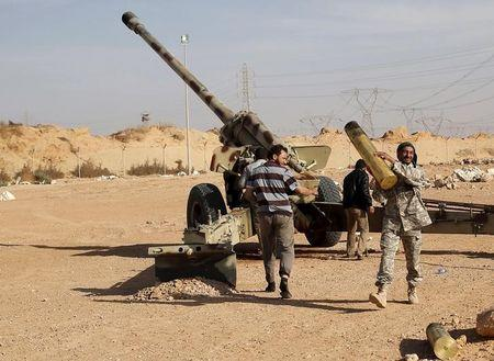 Libya Dawn fighters prepare to fire an artillery cannon at IS militants near Sirte