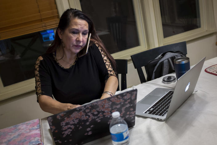 """Natalie Abbas sits at her dining room table, in her """"Command Post,"""" in Myersville, Md., Tuesday, Jan. 19, 2021, the day before the presidential inauguration. Abbas, 59, says her conviction that the election was stolen from Trump is as strong as her belief in God. (AP Photo/Cliff Owen)"""