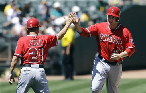 Los Angeles Angels' Mark Trumbo (44) celebrates with third base coach Dino Ebel (21) after hitting a solo home run off of Oakland Athletics pitcher Tommy Milone during the sixth inning of a baseball game in Oakland, Calif., Wednesday, May 1, 2013. (AP Photo/Jeff Chiu)