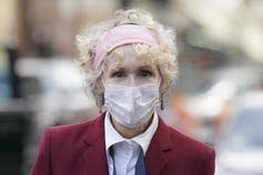 E. Jean Carroll, wearing a mask, arrives at a courthouse.