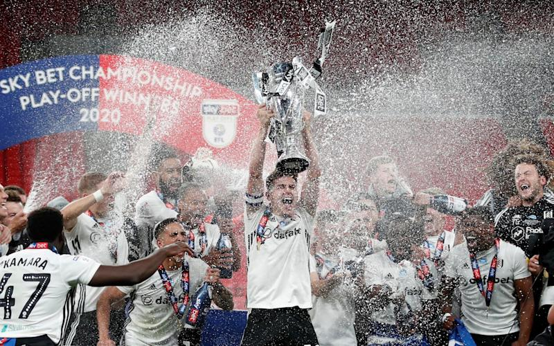 Fulham's Tom Cairney lifts the trophy as he celebrates promotion to the premier league with teammates after winning the match, as play resumes behind closed doors following the outbreak of the coronavirus disease. - REUTERS