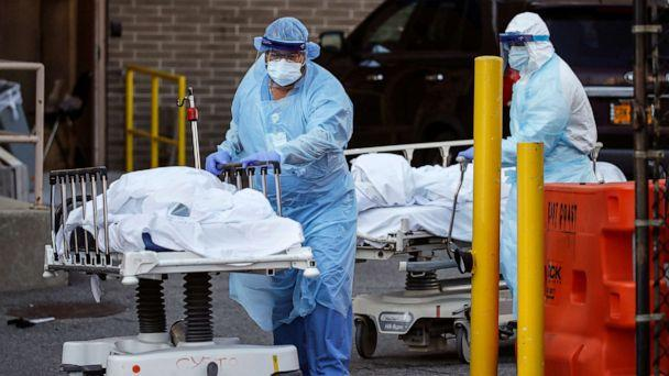 PHOTO: Medical workers wearing personal protective equipment wheel bodies to a refrigerated trailer serving as a makeshift morgue at Wyckoff Heights Medical Center, April 6, 2020, in the Brooklyn borough of New York. (John Minchillo/AP)
