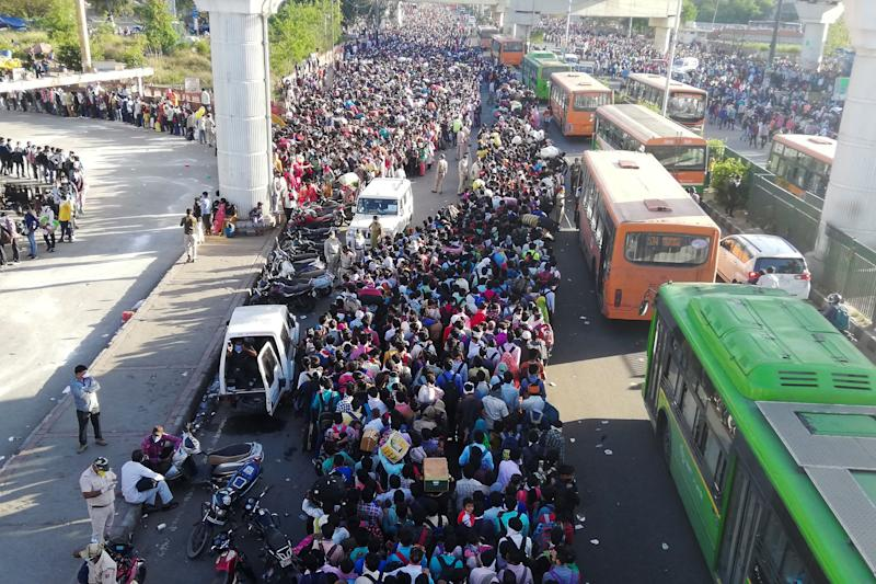 Migrant workers and their family members lineup outside the Anand Vihar bus terminal in New Delhi on March 18 to leave for their villages during a government-imposed nationwide lockdown.   Bhuvan Bagga–AFP/Getty Images