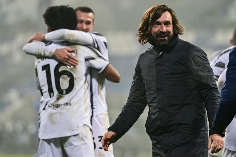 Andrea Pirlo (R) celebrates his first coaching trophy as Juventus beat Napoli in the Italian Super Cup.