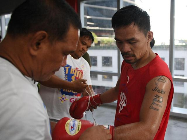 Philippine boxing legend Manny Pacquiao unlaces his gloves after training at a gym in Manila ahead of his world welterweight boxing championship bout against Argentina's Lucas Matthysse in July. (AFP Photo/TED ALJIBE)
