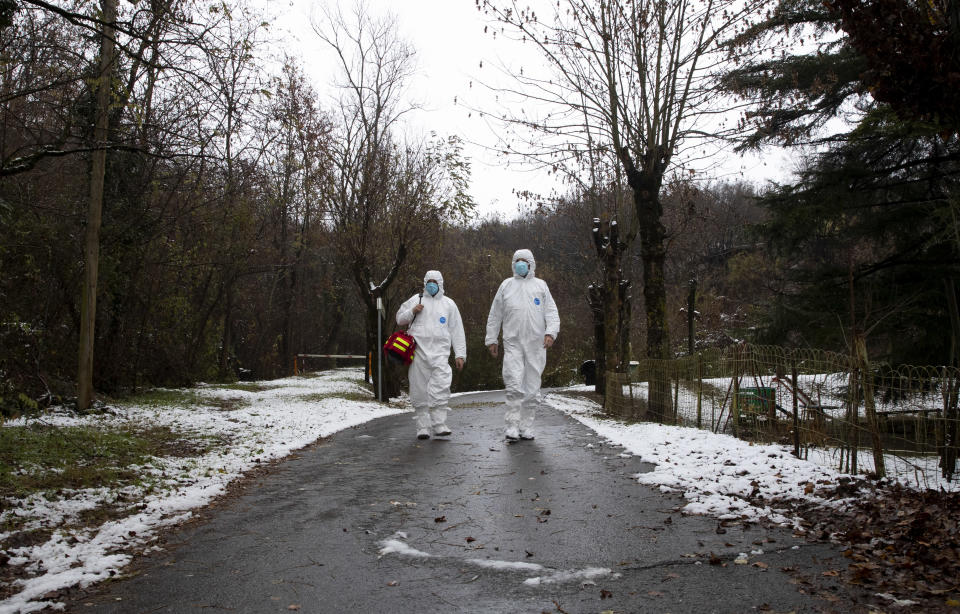 Doctor Luigi Cavanna, right, walks with his nurse assistant Gabriele Cremona after doing a house call on a COVID-19 patient, in Travo, near Piacenza, Italy, Wednesday, Dec. 2, 2020. (AP Photo/Antonio Calanni)