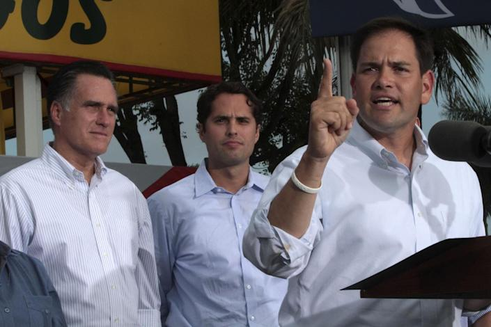 Republican presidential candidate, former Massachusetts Gov. Mitt Romney, left, and his son Craig, center, listen as Sen. Marco Rubio R-Fla., speaks at a campaign event at El Palacio de los Jugos, Monday, Aug. 13, 2012, in Miami, Fla. (AP Photo/Mary Altaffer)