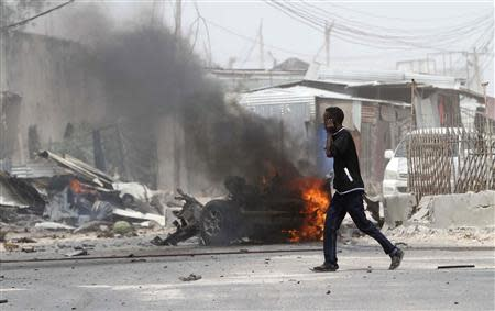 A man talks on his mobile phone as he walks at the scene of an explosion near the entrance of the airport in Somalia's capital Mogadishu