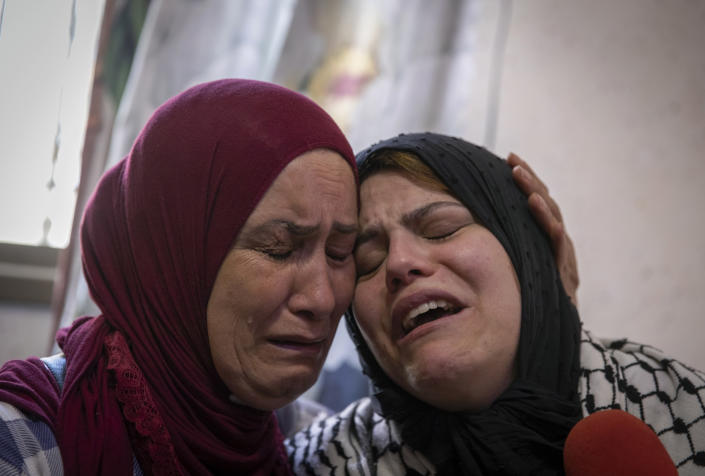 Palestinian Nevin Abu Arab, 49, right, cries with a relative mourner during the funeral of her son Ahmed Jamil Fahed, in the West Bank refugee camp of al-Amari, Ramallah, Tuesday, May 25, 2021. Fahed was shot and killed by undercover Israeli forces early Tuesday near Ramallah, according to the Palestinian Authority's official Wafa news agency. (AP Photo/Nasser Nasser)