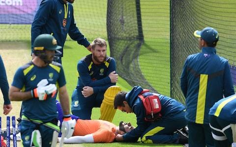 Australia's David Warner (C) looks on as an injured net bowler receives medical attention during a training session - Credit: afp