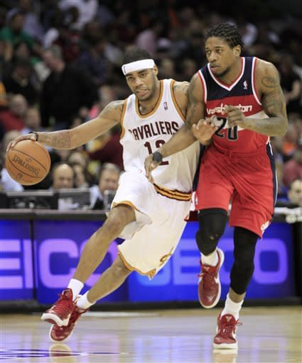 Cleveland Cavaliers' D.J. Kennedy (12) drives to the basket under pressure from Washington Wizards' Cartier Martin (20) in the second quarter in an NBA basketball game on Wednesday, April 25, 2012, in Cleveland. (AP Photo/Tony Dejak)