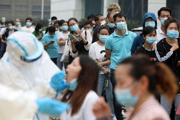 PHOTO: People line up for medical workers to take swabs for the COVID-19 test at a large factory in Wuhan in central China's Hubei province on May 15, 2020. (Chinatopix via AP)