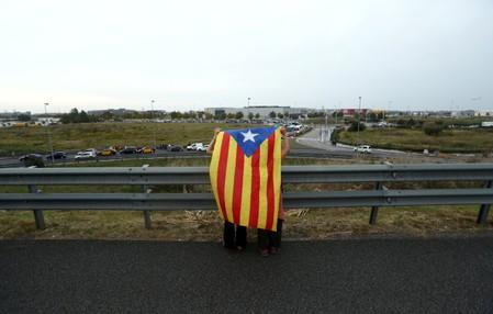 Protesters hold an Estelada (Catalan separatist flag) outside the airport in Barcelona