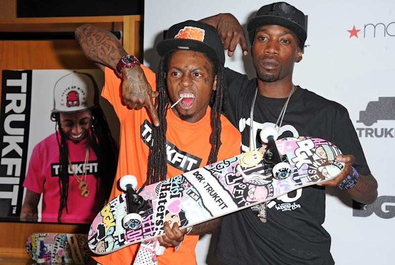 This June 1, 2012 file photo shows Grammy Award winning hip hop artist Lil Wayne, left, and professional skateboarder Stevie Williams celebrating at the launch of their contemporary clothing lines TRUKFIT and DGK at Macy's stores in Los Angeles. (Photo by Katy Winn/Invision, file)