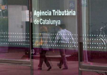A couple is reflected on a glass of the Catalan Tax Agency in Barcelona, Spain, September 18, 2017. REUTERS/Albert Gea